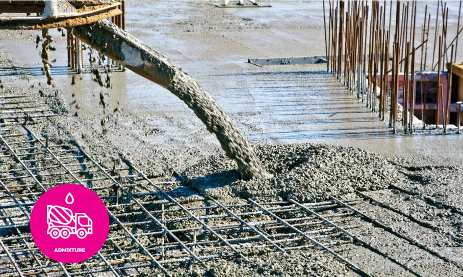 An advanced concrete waterproofing admixture being pumped and placed over steel reinforcing at a construction site