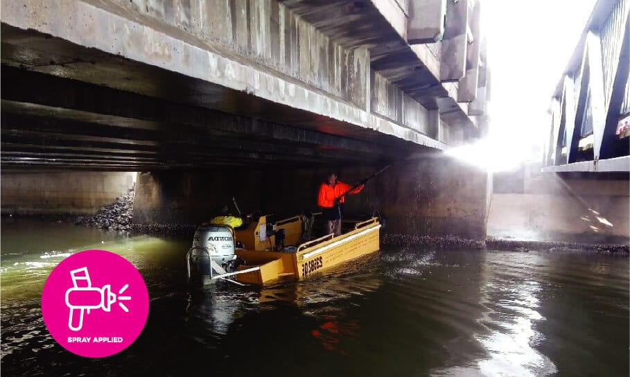 AQURON 7000 - Durability enhancement treatment for new and existing concrete being applied to the underside of a concrete bridge from a boat